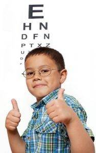 Boy in glasses in front of eye chart, optometrist, Concord, NC